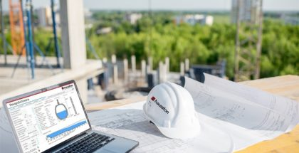 Hydraulic calculation software on laptop at construction site